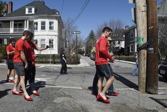 Men from Boston University wear red, women's high-heeled shoes while walking twice around Cypress Field during Brookline's first annual Walk a Mile in Her Shoes, an international men's march to stop rape, sexual assault, and gender violence on Sunday, Apr. 12, 2015.