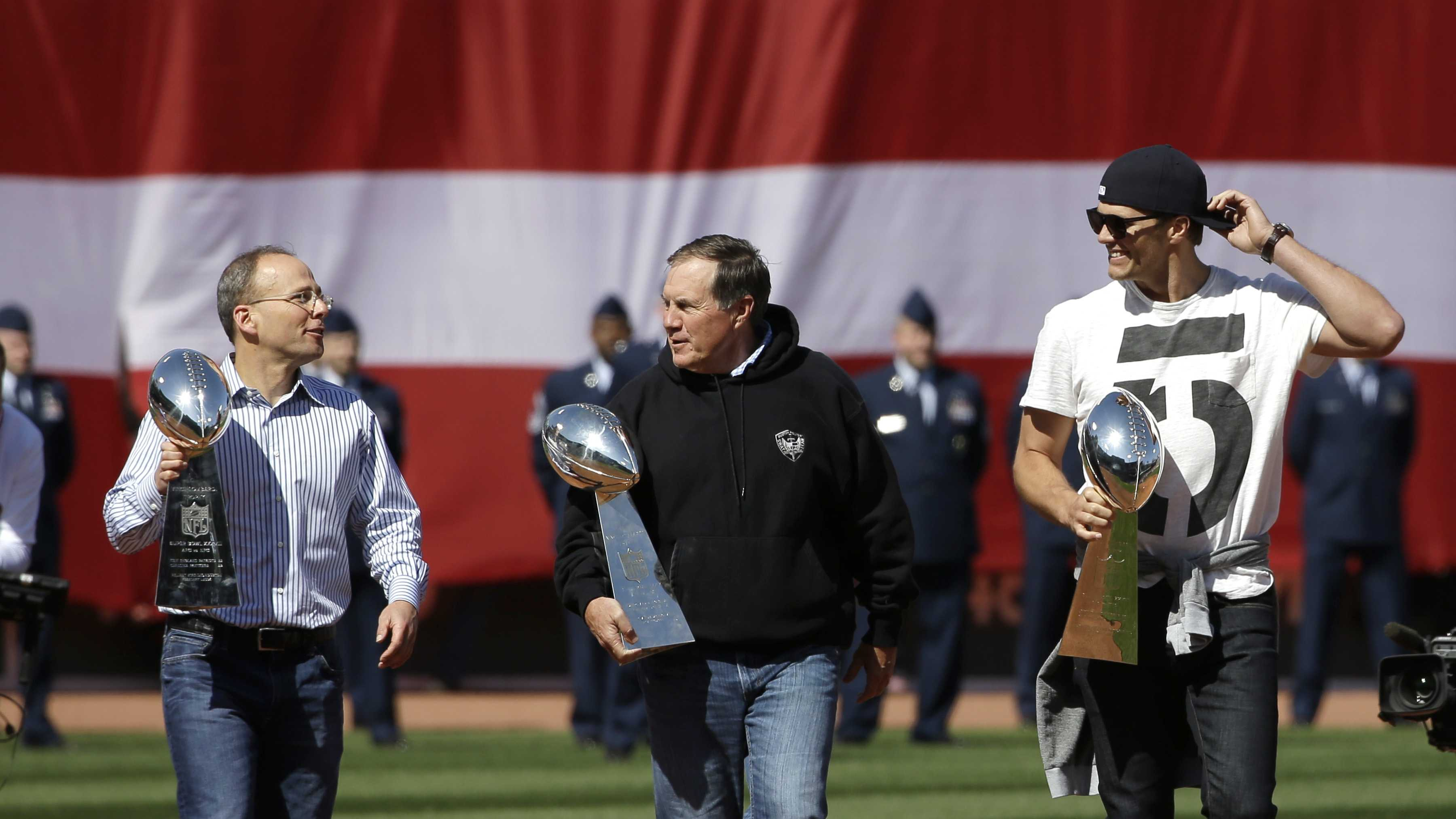 New England Patriots, from the left, President Jonathan Kraft, head coach Bill Belichick, and quarterback Tom Brady, each hold a Super Bowl trophy as they step on to the field at Fenway Park before a baseball game between the Boston Red Sox and the Washington Nationals, Monday, April 13, 2015, in Boston.