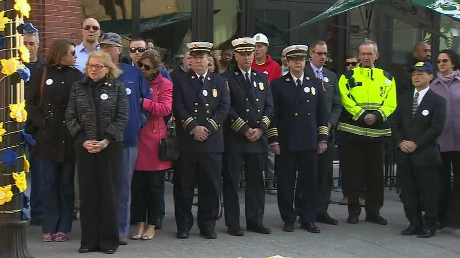 Boston firefighters and first responders look on.