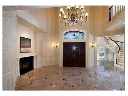 Grand two story foyer with bridal staircase, opens to a cathedral great room with fireplace and built in cabinetry