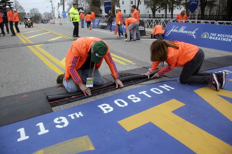 Race officials set up electronics at the starting line of the Boston Marathon, Monday, April 20, 2015, in Hopkinton, Mass.