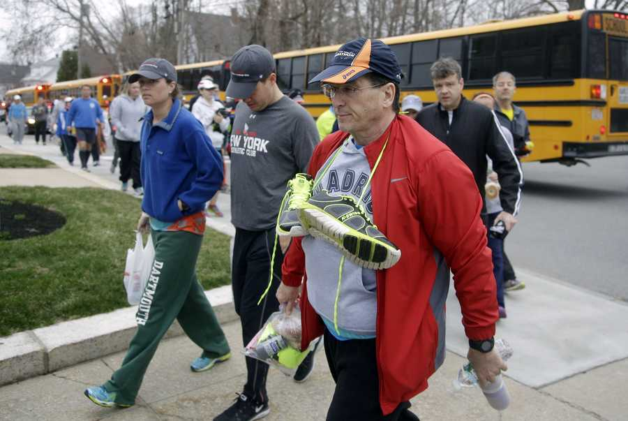 Runners get off buses for the start of the Boston Marathon