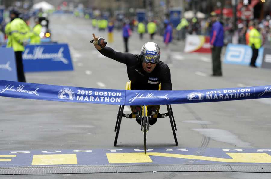Marcel Hug, of Switzerland, crosses the finish line to win the wheelchair division of the Boston Marathon, Monday, April 20, 2015, in Boston.