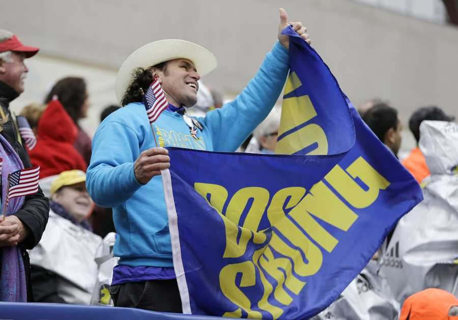 "Carlos Arredondo, a 2013 Boston Marathon first-responder, holds a ""Boston Strong"" banner in the grandstand near the Boston Marathon finish line, Monday, April 20, 2015, in Boston."