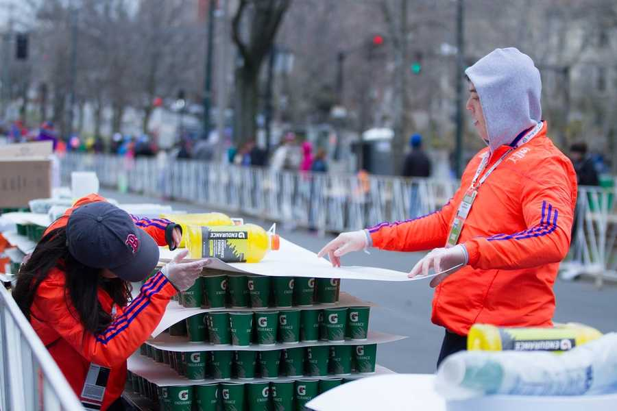 Volunteers are preparing water for marathon runners near the 24 miles spot. They are using paper and bottles of water to cover the cups because of the wind.