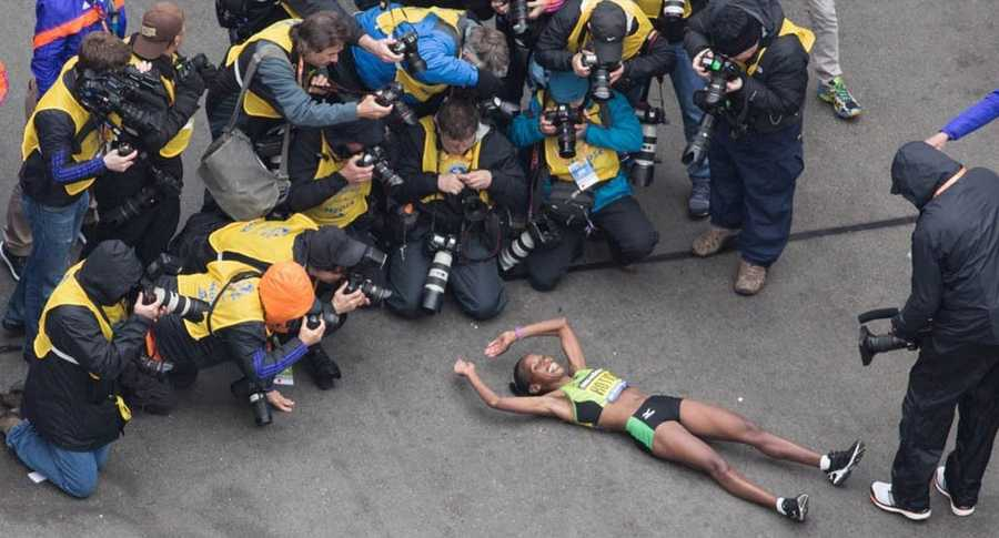 Caroline Rotich lies down after crossing the finish line.