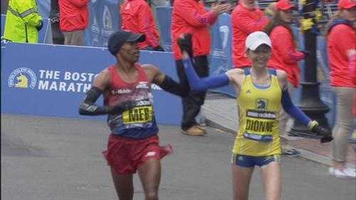 Last year's winner Meb Keflezighi holds the hand of Hillary Dionne while crossing the finish line.
