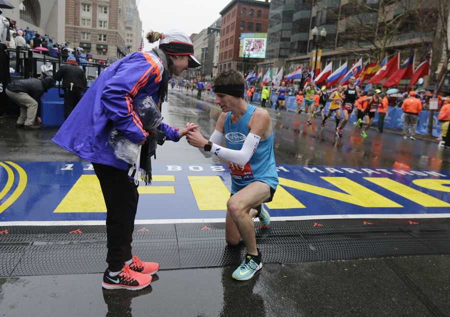 Dustin Hicks, right, of Temple Terrace, Fla., proposes to Laura Bowerman after crossing the finish line of the Boston Marathon, Monday, April 20, 2015, in Boston.
