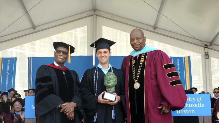 University of Massachusetts Provost Winston Langley, left, and Chancellor J. Keith Motley with Shaun O'Grady, holding the John F. Kennedy Award for Academic Excellence.