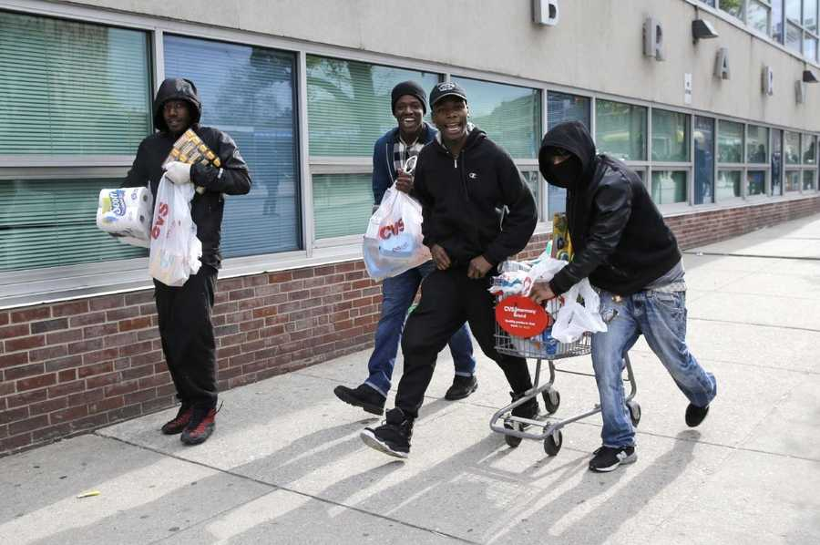 Men carry items, Monday, April 27, 2015, during unrest following the funeral of Freddie Gray in Baltimore. Gray died from spinal injuries about a week after he was arrested and transported in a Baltimore Police Department van.