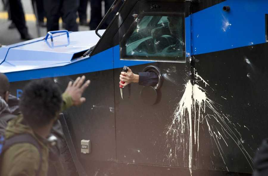 Baltimore police officer sprays pepper spray to demonstrators after the funeral of Freddie Gray, Monday, April 27, 2015, at New Shiloh Baptist Church in Baltimore. Gray died from spinal injuries about a week after he was arrested and transported in a Baltimore Police Department van.
