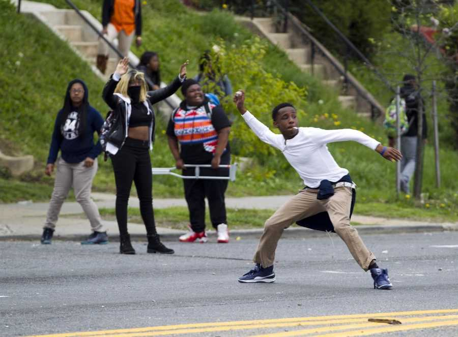 Demonstrators throw rocks at the police after the funeral of Freddie Gray on Monday, April 27, 2015, at New Shiloh Baptist Church in Baltimore. Gray died from spinal injuries about a week after he was arrested and transported in a Baltimore Police Department van.