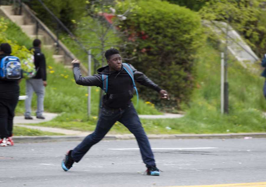 A demonstrator throws a rock at the police after the funeral of Freddie Gray on Monday, April 27, 2015, at New Shiloh Baptist Church in Baltimore. Gray died from spinal injuries about a week after he was arrested and transported in a Baltimore Police Department van.
