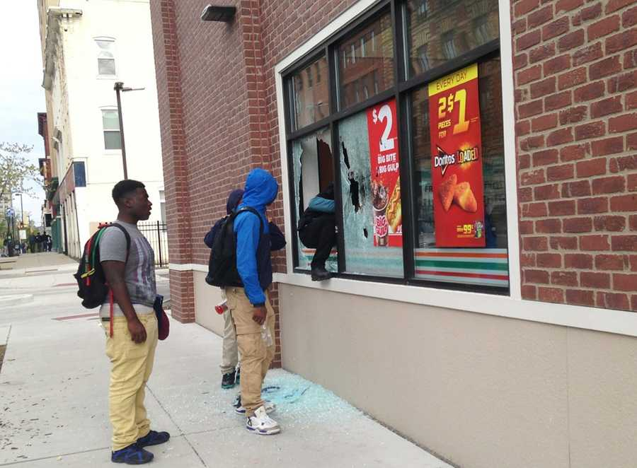 A person climbs through a broken window at a convenience store in west Baltimore on Monday, April 27, 2015. Demonstrators clashed with police after the funeral of Freddie Gray. Gray died from spinal injuries about a week after he was arrested and transported in a Baltimore Police Department van.