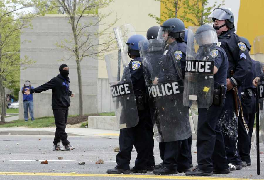 A demonstrator taunts police as they respond to thrown objects, Monday, April 27, 2015, after the funeral of Freddie Gray in Baltimore. Gray died from spinal injuries about a week after he was arrested and transported in a Baltimore Police Department van.