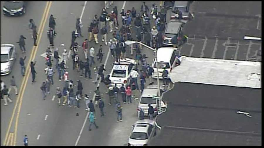 Rioters use baseball bats to smash a Baltimore Police Department vehicle.