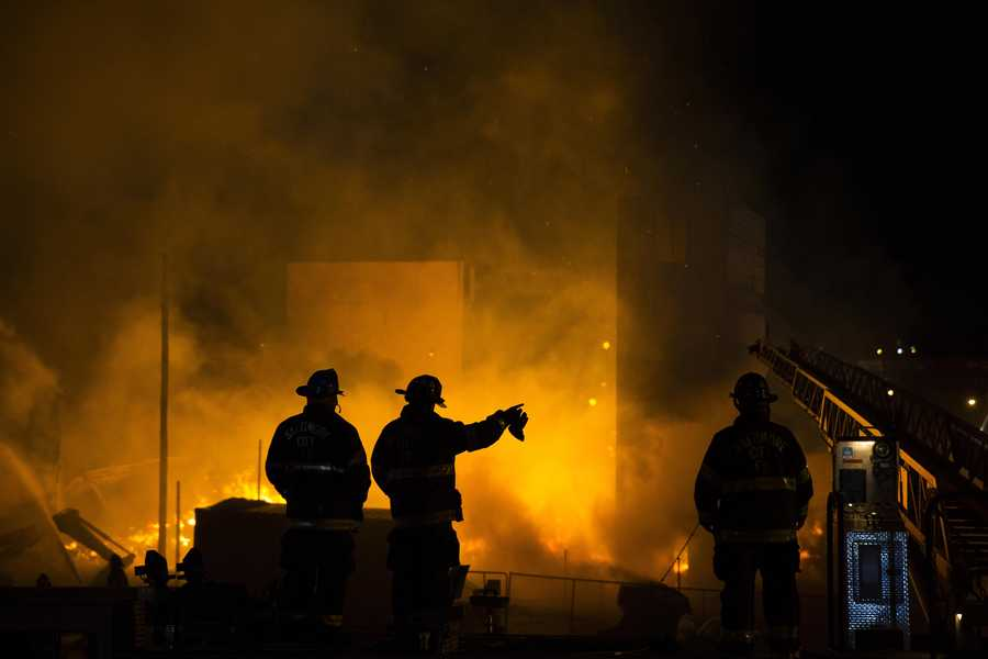 Firefighters battle a blaze, Monday, April 27, 2015, after rioters plunged part of Baltimore into chaos, torching a pharmacy, setting police cars ablaze and throwing bricks at officers. (AP Photo/Evan Vucci)