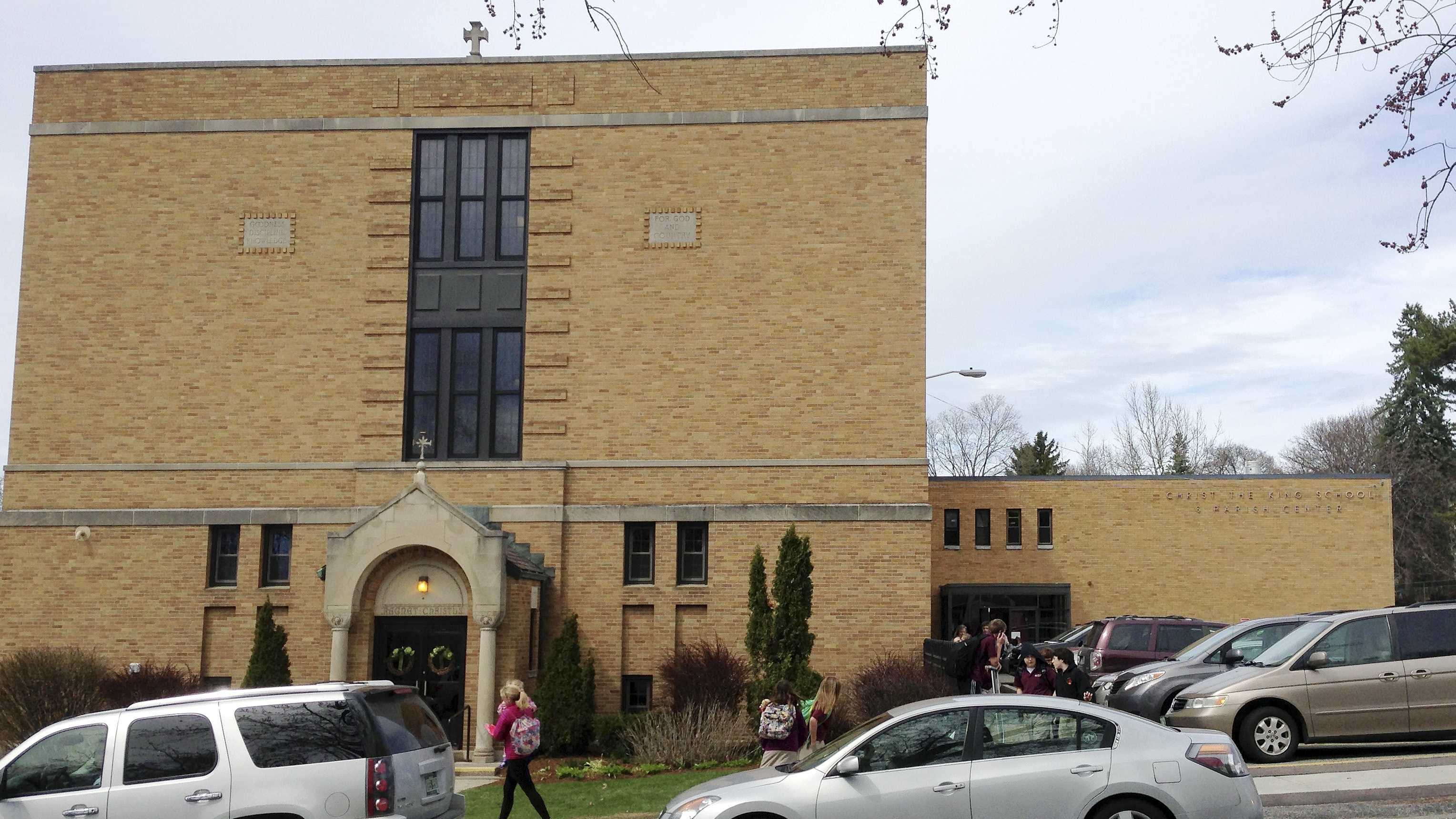 In this April 29, 2015 photo, parents pick up their children at the end of the school day at Christ the King School in Burlington, Vt. The church's sound system that plays recorded bells and hymns has struck a chord with some neighbors, who find it noisy and intrusive.