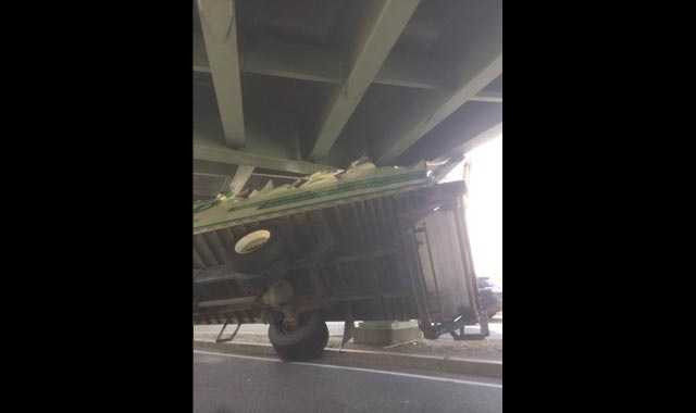 The top of a tractor-trailer is sheared off after hitting an overpass on Storrow Drive.