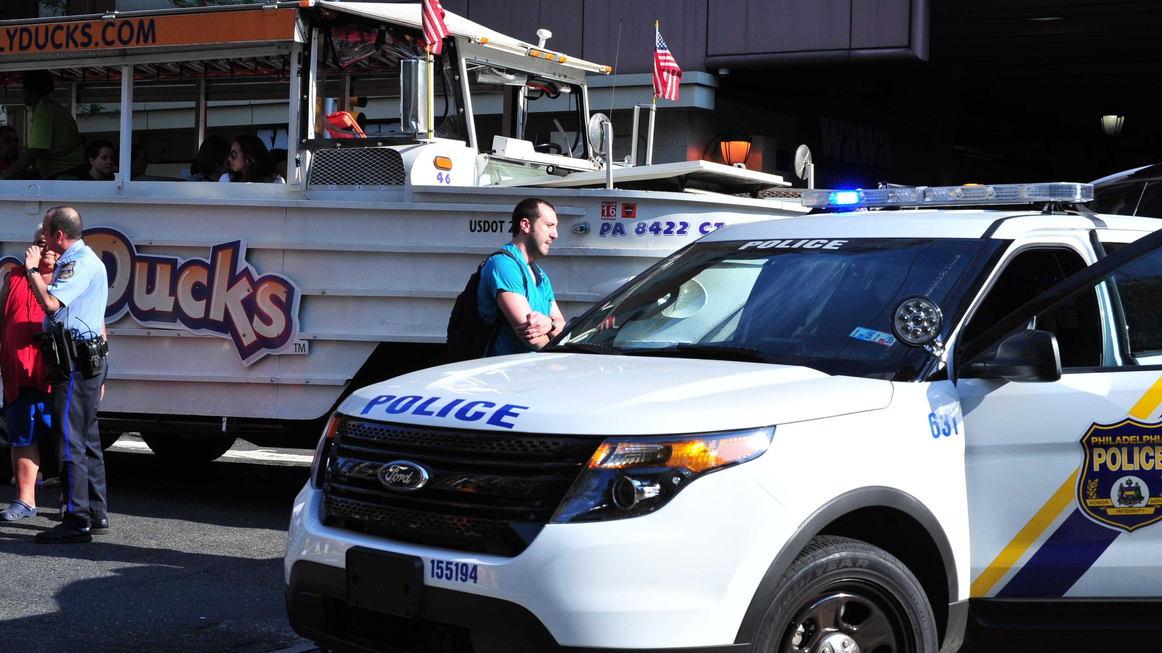 A Philadelphia police officer, left, interviews the husband of a victim who was struck and killed by a Duck Boat near the Philadelphia Convention Center. Police say a Ride the Ducks trolley ran over the woman Friday evening in the Chinatown neighborhood.