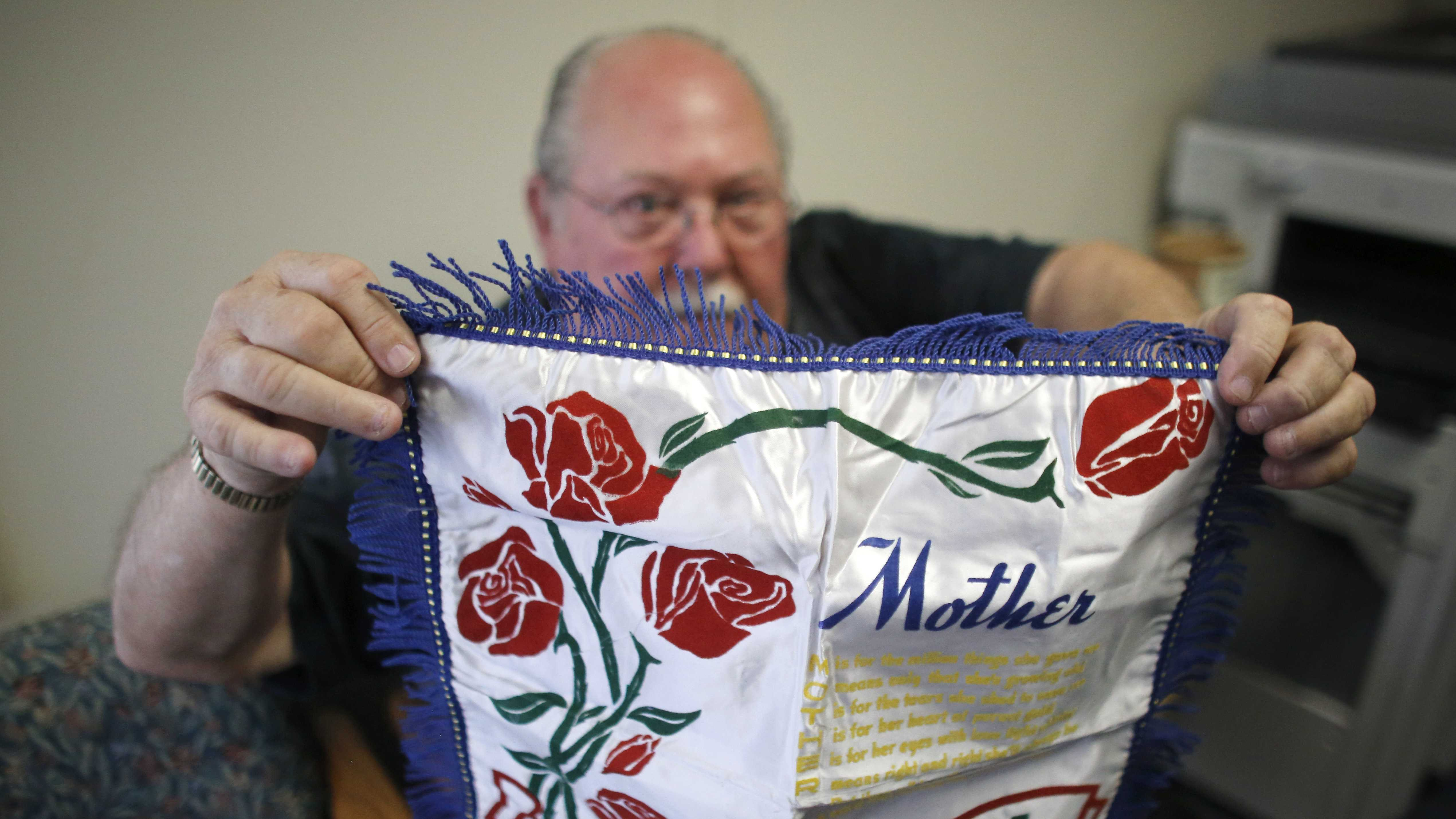 In this photo taken, Tuesday, May 5, 2015, Don Lamoureux displays a World War II era pillow sham at a senior center in Millville, Mass., which his son purchased from an online auction site. Dominic O'Gara had mailed the elaborate pillow sham from his U.S. Army base in California to his mother in Millville in 1942. The Lamoureux's tried to find the soldier's relatives to give it to them, but were unable to find any. The plan now is to put the sham on display in the town's senior center, just yards from the house where the O'Gara family once lived.