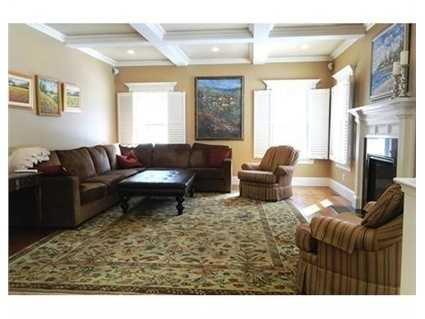 Spacious family room with coffered ceiling, and fireplace.