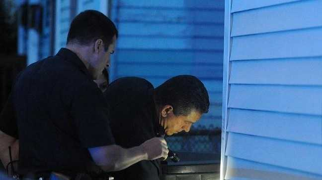 Two Fall River police officers look at the corner of a house for evidence after a shooting around 8 p.m. on Friday evening at the corner of Wade and Fifth streets.