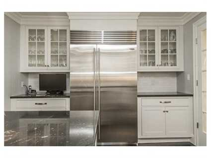 "A 48"" Sub-Zero built-in side-by-side refrigerator, 48"" Thermador Pro Grande professional series 6-burner gas range/steam and convection oven complete the kitchen."