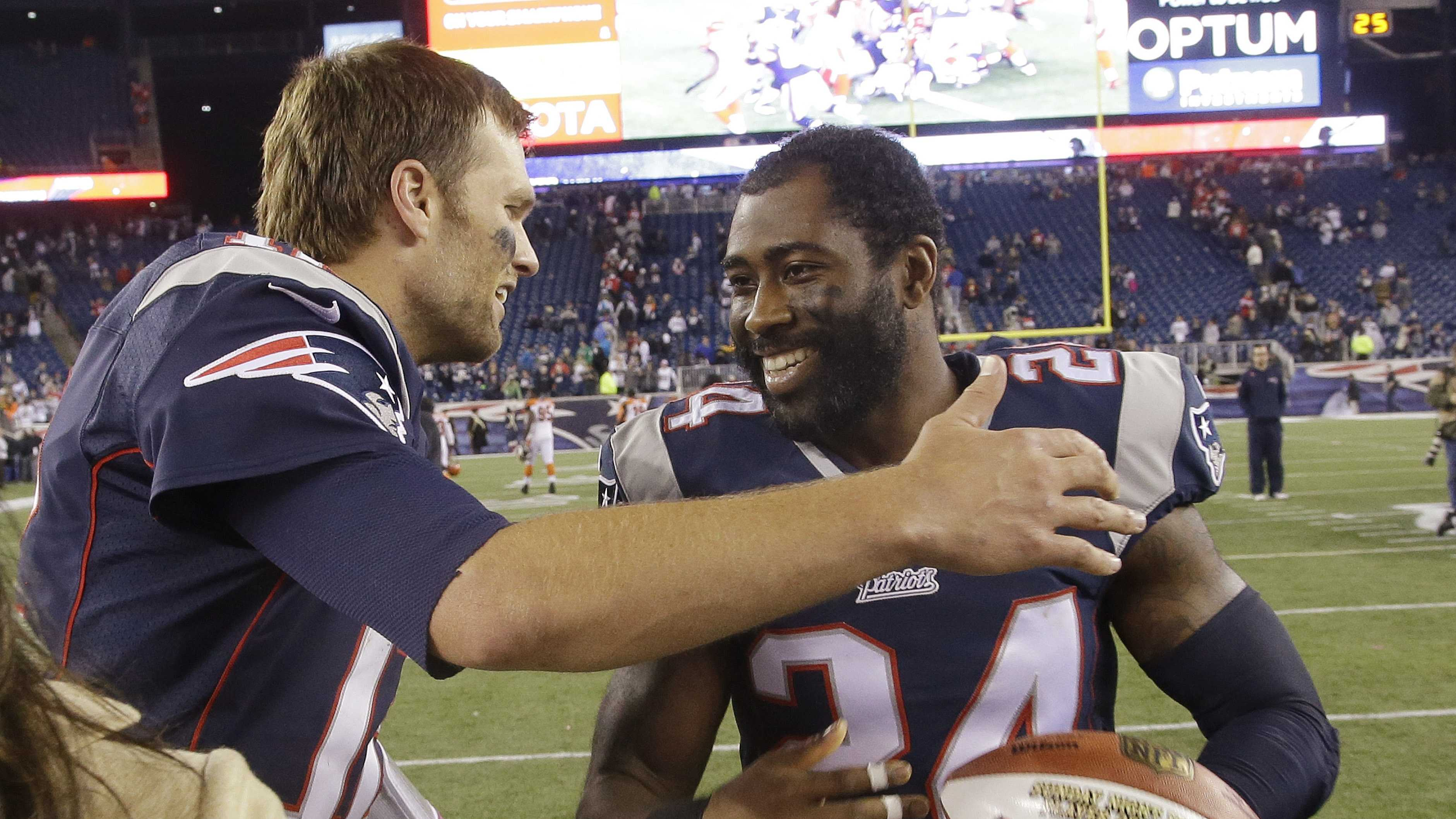 New England Patriots quarterback Tom Brady (12) hugs cornerback Darrelle Revis (24) after their NFL football game against the Cincinnati Bengals Sunday, Oct. 5, 2014, in Foxborough, Mass.