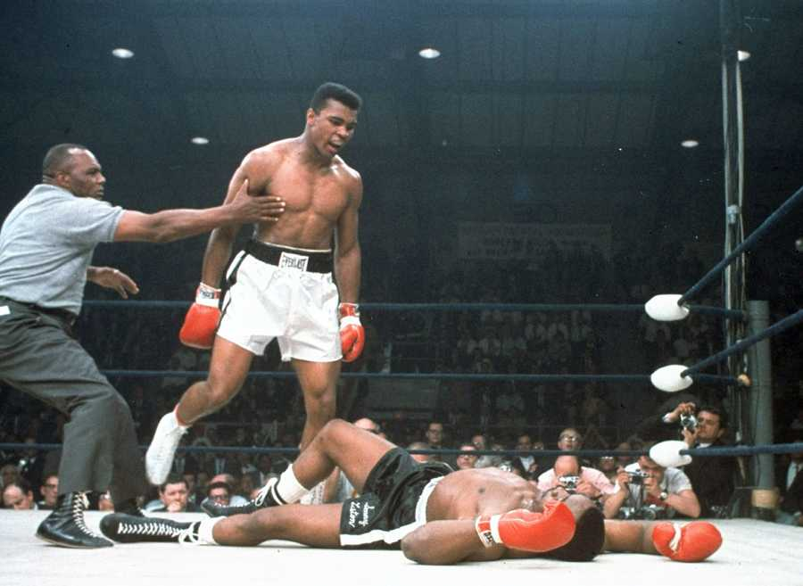 In this May 25, 1965, file photo, heavyweight champion Muhammad Ali is held back by referee Joe Walcott, left, after Ali knocked out challenger Sonny Liston in the first round of their title fight in Lewiston, Maine. The bout produced one of the strangest finishes in boxing history as well as one of sports' most iconic moments.