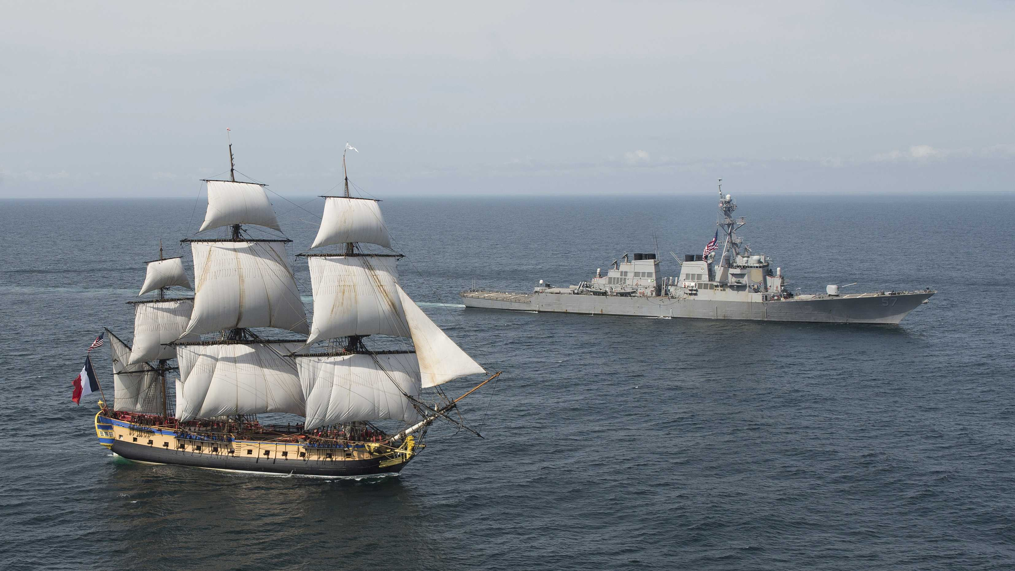 In this Tuesday, June 2, 2015 image provided by the U.S. Navy, the Arleigh Burke-class guided-missile destroyer USS Mitscher, right, welcomes the French tall ship replica Hermione in the vicinity of the Battle of Virginia Capes off the East Coast of the United States.