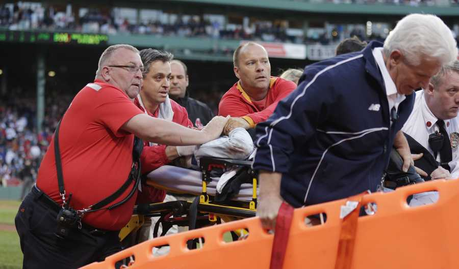 Boston Red Sox medical personnel tend to a woman, who with was hit by a wooden shard, off a broken bat of Oakland Athletics' Brett Lawrie, in the second inning. The game stopped as the woman was taken from the stands on a stretcher down the first base line to a waiting ambulance.