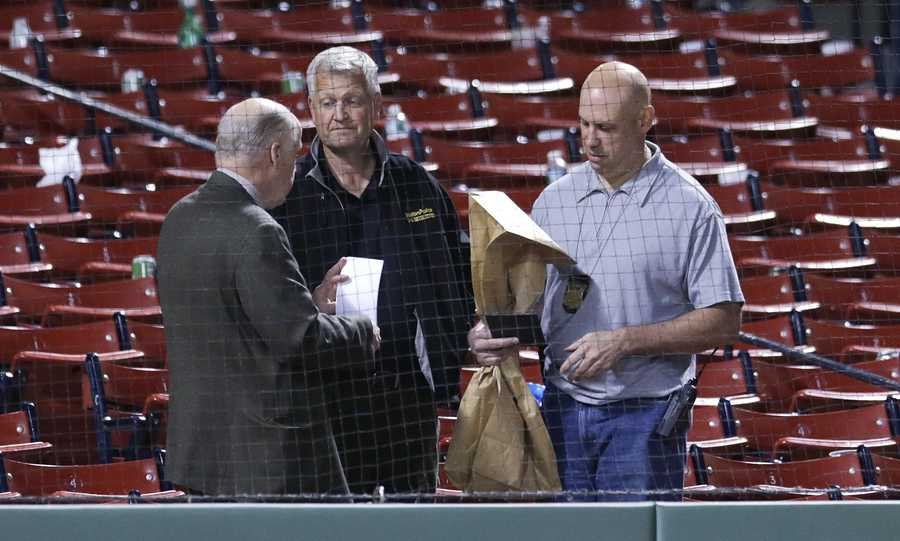 Boston Police detectives take notes and hold an evidence bag as they confer at the site where a woman was struck by a wooden shard, off a broken bat by Oakland Athletics Brett Lawrie, following a baseball game at Fenway Park in Boston, Friday, June 5, 2015.