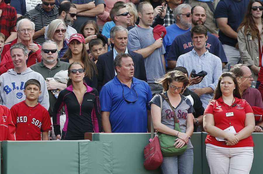 Fans observe a moment of silence before a baseball game between the Boston Red Sox and the Oakland Athletics, at Fenway Park in Boston, Saturday, June 6, 2015, in the area of the stands where a woman was hit and seriously injured by a broken bat during Friday's game.