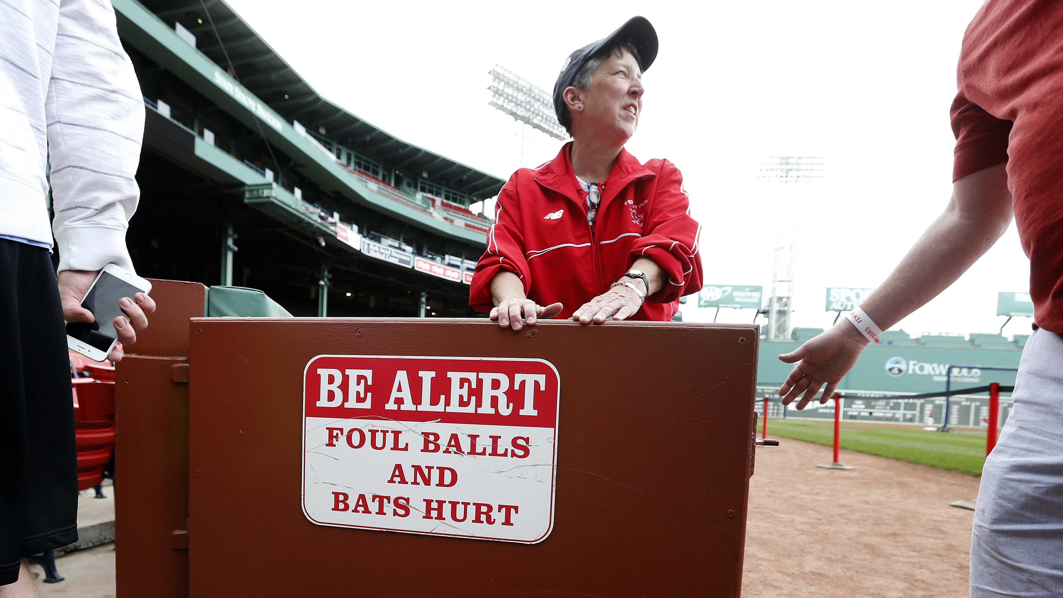 A tour guide at Fenway Park holds open a door to the stands which displays a warning sign, Saturday, June 6, 2015, before a baseball game between the Boston Red Sox and the Oakland Athletics in Boston. A woman was hit and seriously injured by a broken bat during the game on Friday.