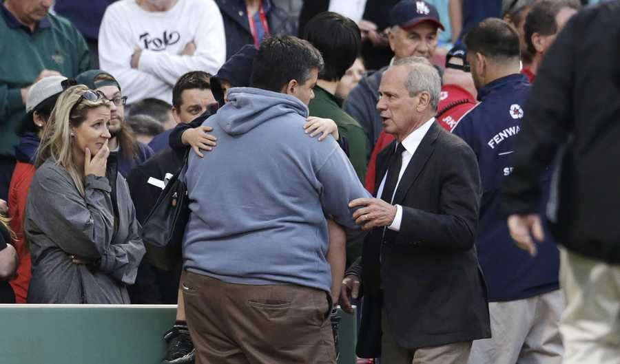 Boston Red Sox president and CEO Larry Lucchino comforts a man holding a child after a woman they were sitting with was hit by a wooden shard, off a broken bat of Oakland Athletics' Brett Lawrie.