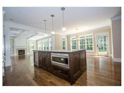 A spacious eat in kitchen with custom cabinets and a large granite island for six.