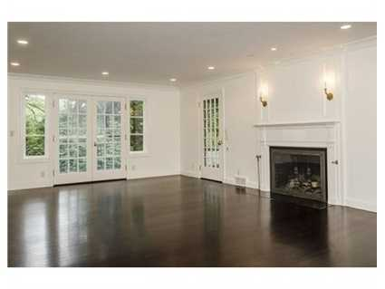 Stately living room with fireplace and French doors to a screened porch and beautiful private garden.
