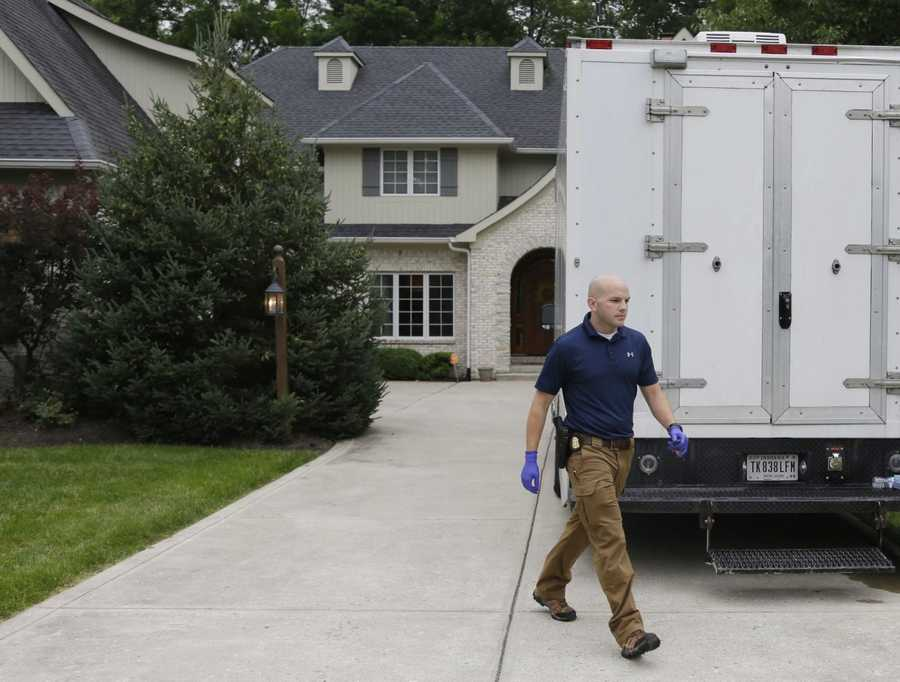 Federal authorities walk outside of the home of Subway restaurant spokesman Jared Fogle, Tuesday, July 7, 2015, in Zionsville, Ind. FBI agents and Indiana State Police have removed electronics from the property.