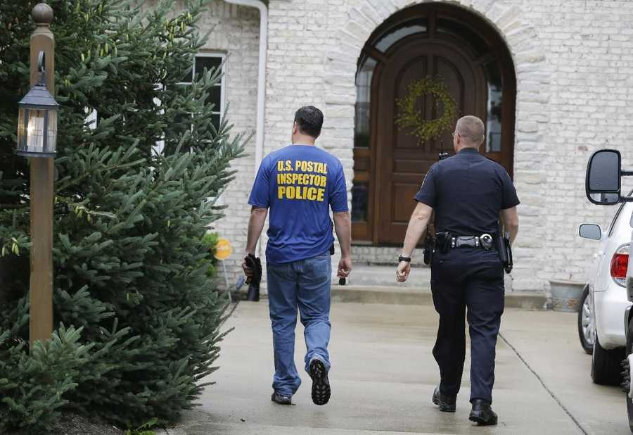 Federal authorities and a Zionsville police office arrive at the home of Subway restaurant spokesman Jared Fogle Tuesday, July 7, 2015, in Zionsville, Ind. FBI agents and Indiana State Police have removed electronics from the property.