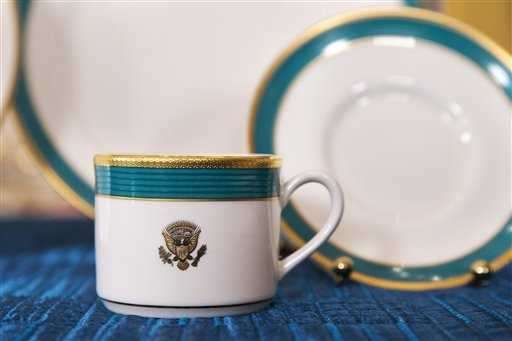 "A cup and saucer, part of the new Obama state china service, feature a fluted band of ""Kailua Blue"" framed by a textured gold rim."