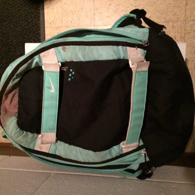 A black Nike backpack with teal trim.