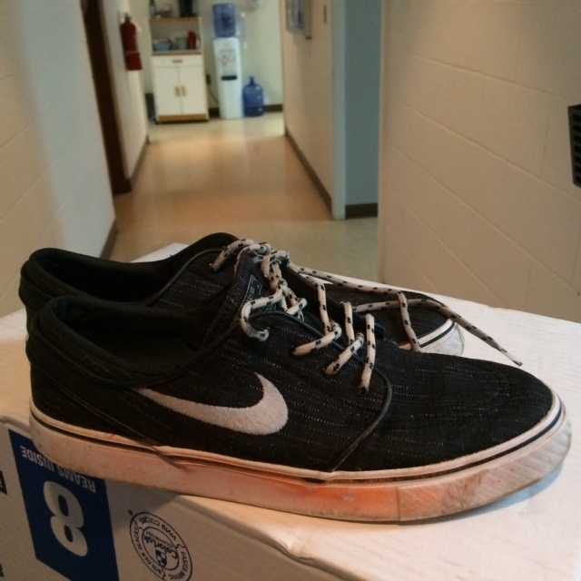 Size 9 1/2 black Nike sneakers with white soles.
