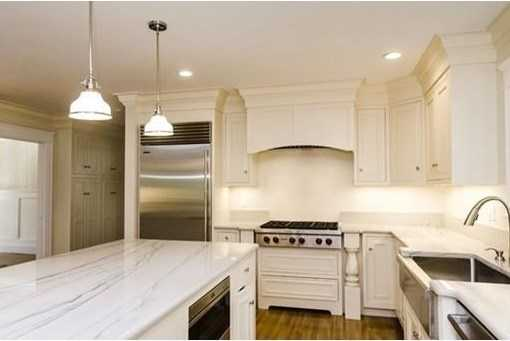 Kitchen flows into second dining area and family room with skylights and French doors leading to a limestone patio.