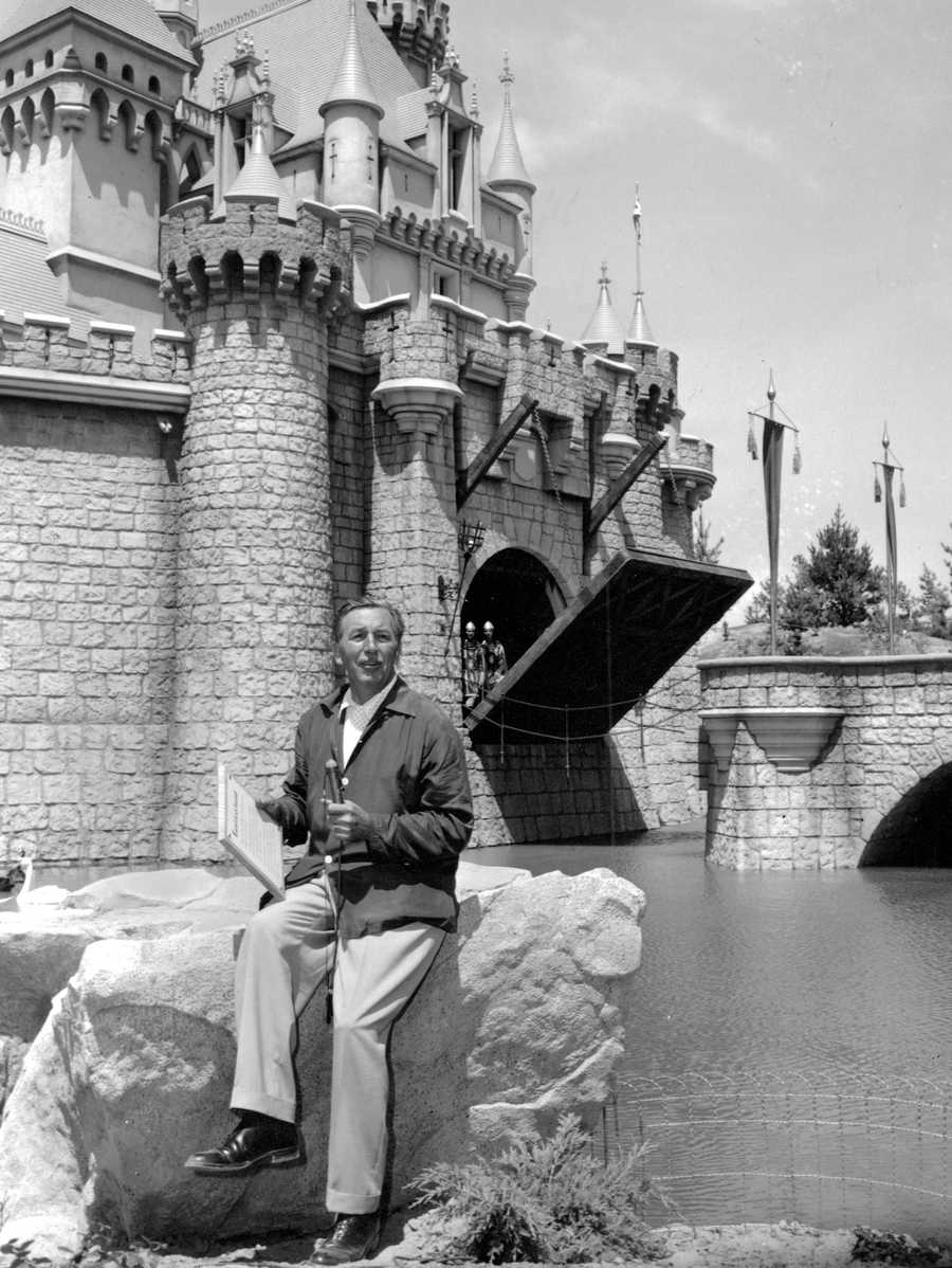 In this Sunday, July 17, 1955 file photo, Walt Disney sits on a rock in front of the Sleeping Beauty Castle in the Fantasyland section of Disneyland on opening day of the amusement theme park in Anaheim, Calif. A year earlier, Disney made his move. He succumbed to the lure of television and arranged to tie in the TV show (he hosted) with a Disneyland park.