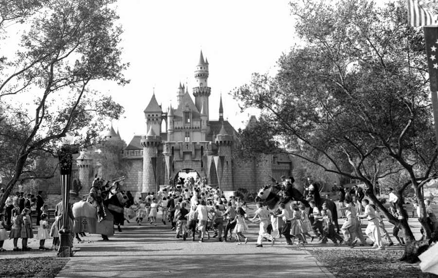 In this Sunday, July 17, 1955 file photo, children sprint across a drawbridge and into a castle that marks the entrance to Fantasyland at the opening of Walt Disney's Disneyland in Anaheim, Calif. Fantasyland had been closed until late in the day.