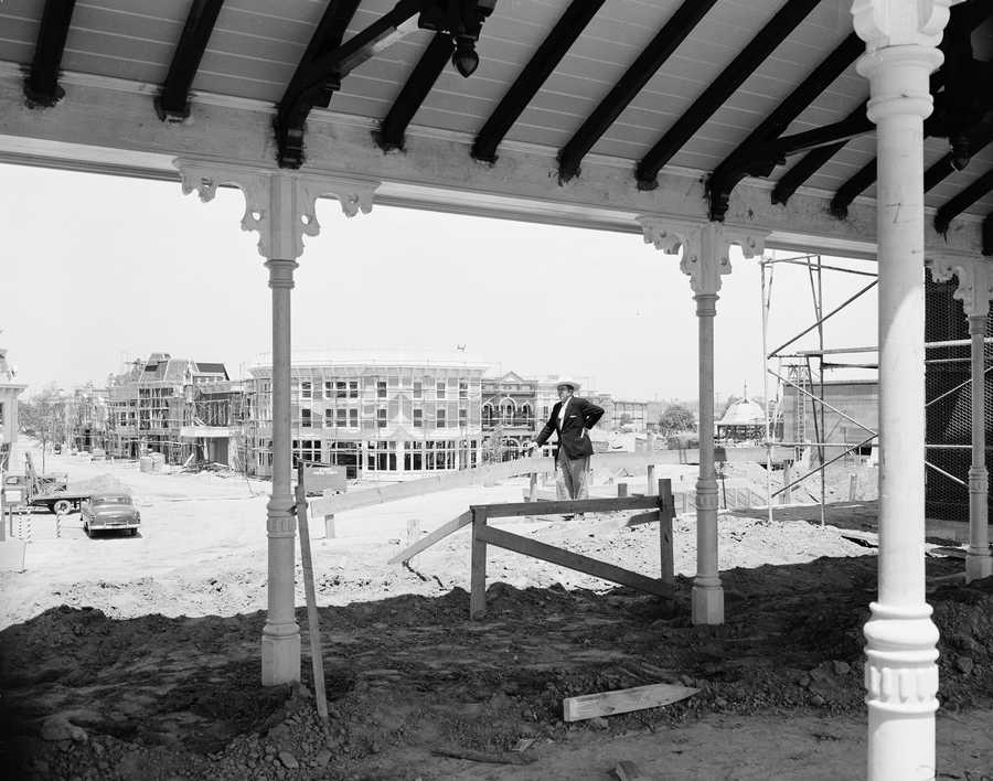 Walt Disney stands framed by the covered waiting room of the Disneyland railroad station on Main Street in Anaheim, Ca., June 9, 1955. Disney is building a 17-million-dollar amusement park. When completed, Main Street will be typical of the years from 1890 to 1910.