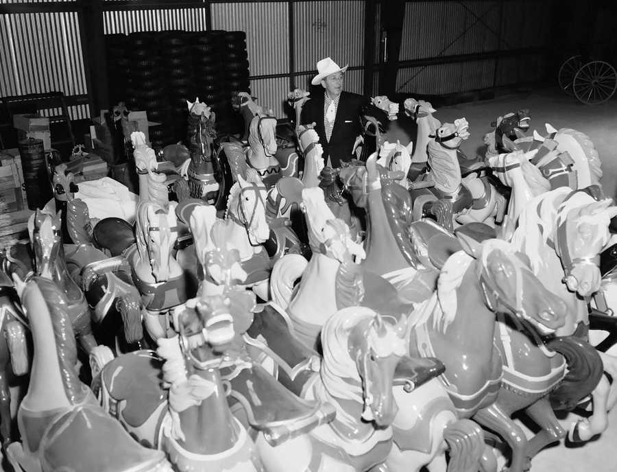 Walt Disney checks over some of the horses that will be used on the huge merry-go-round to be erected in the center of the Fantasyland section of Disneyland at Anaheim, California on June 9, 1955. These are all old, hand-carved horses that Disney scouted the country for and they are being restored to new at the Disneyland workshops.