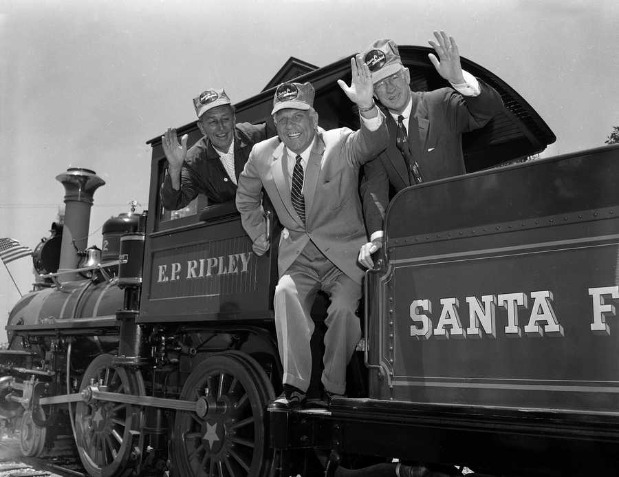 Governor Goodwin J. Knight, of California, center, Walt Disney, left, and Fred G. Gurley, President of Santa Fe Railroad, right, board the cab of an old-time railroad engine to take a ride around Disneyland in Anaheim, Calif. July 17, 1955. Disneyland, 160 acres and 17 million dollars of fun opened its doors today.