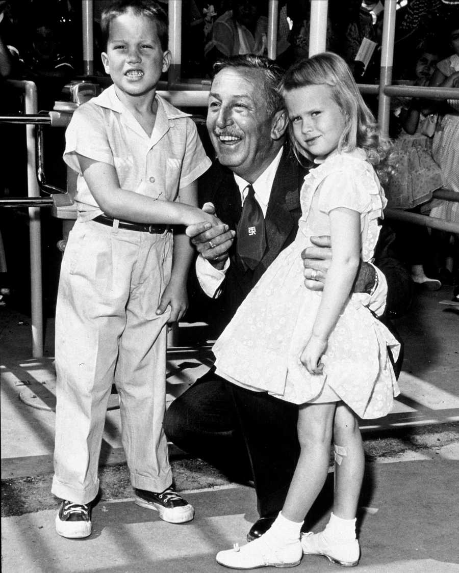 In this handout file photo from Disneyland, Walt Disney poses with the first two visitors, Michael Schwartner, 7, left, and Christine Vess, 5, right, on the park's opening day at Disneyland, July 17, 1955, in Anaheim, Calif. The theme park celebrates its 50th anniversary Sunday.
